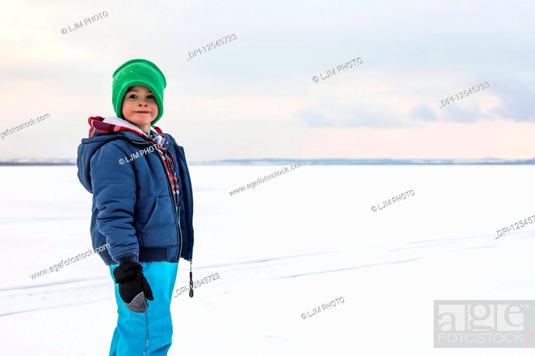 Stock Photo: A young boy walking on a frozen lake while ice fishing during a winter family outing; Wabamun, Alberta, Canada.
