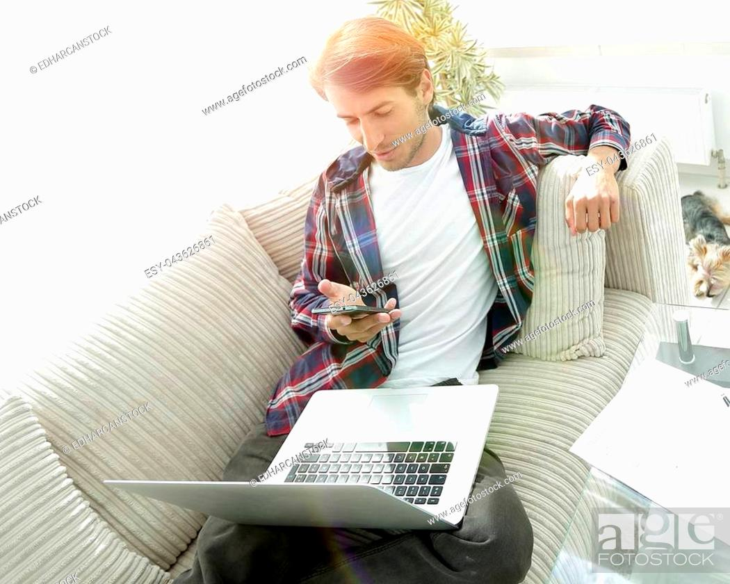 Stock Photo: young man with laptop and smartphone sitting on sofa in living room. photo with copy space.