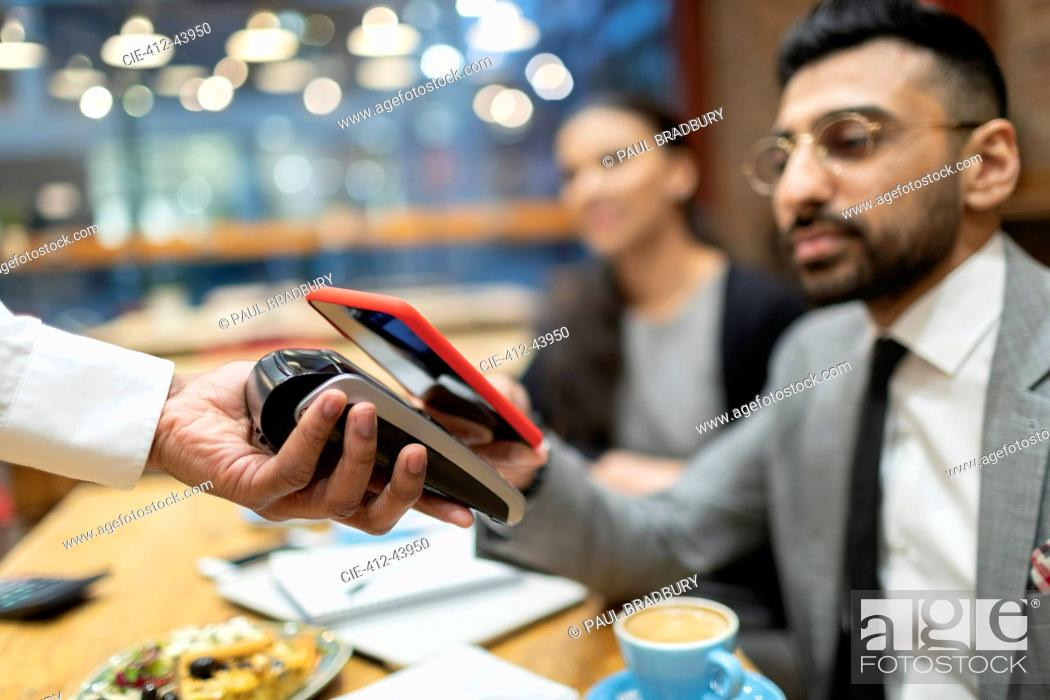 Stock Photo: Businessman in cafe paying with smart phone contactless payment.