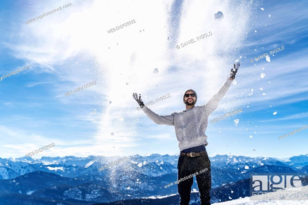 Stock Photo: Germany, Bavaria, Brauneck, man in winter playing with snow in the mountains.