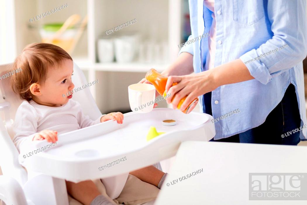 Stock Photo: family, eating, feeding and people concept - little baby and mother pouring natural carrot juice from glass bottle to cup at home kitchen.