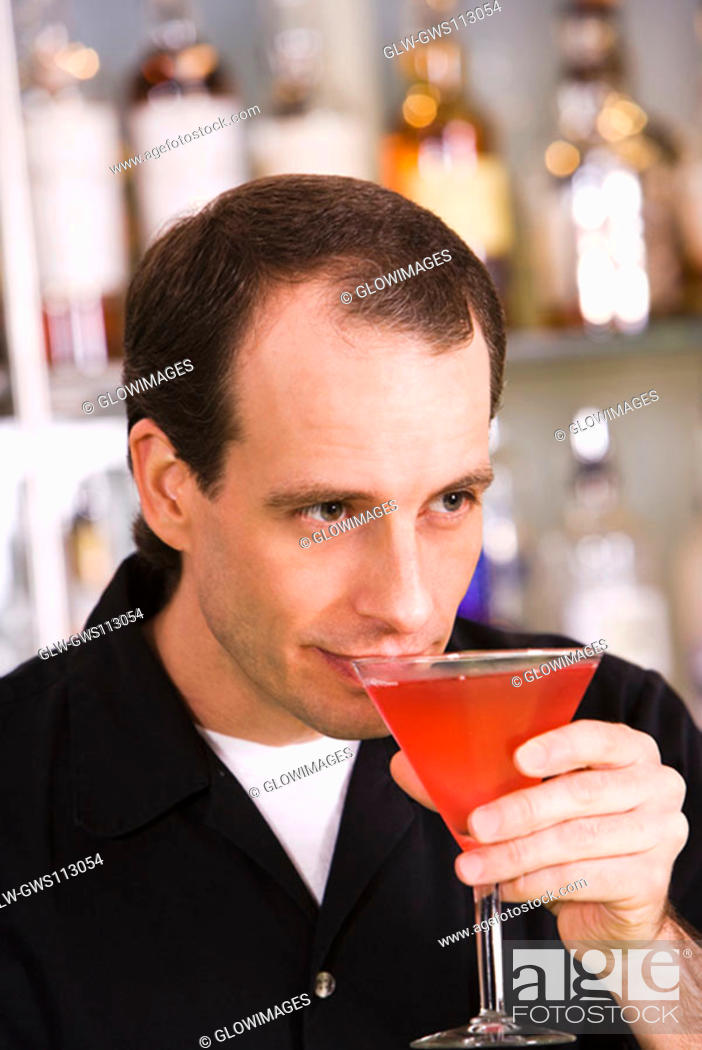 Stock Photo: Close-up of a mid adult man drinking a cocktail.