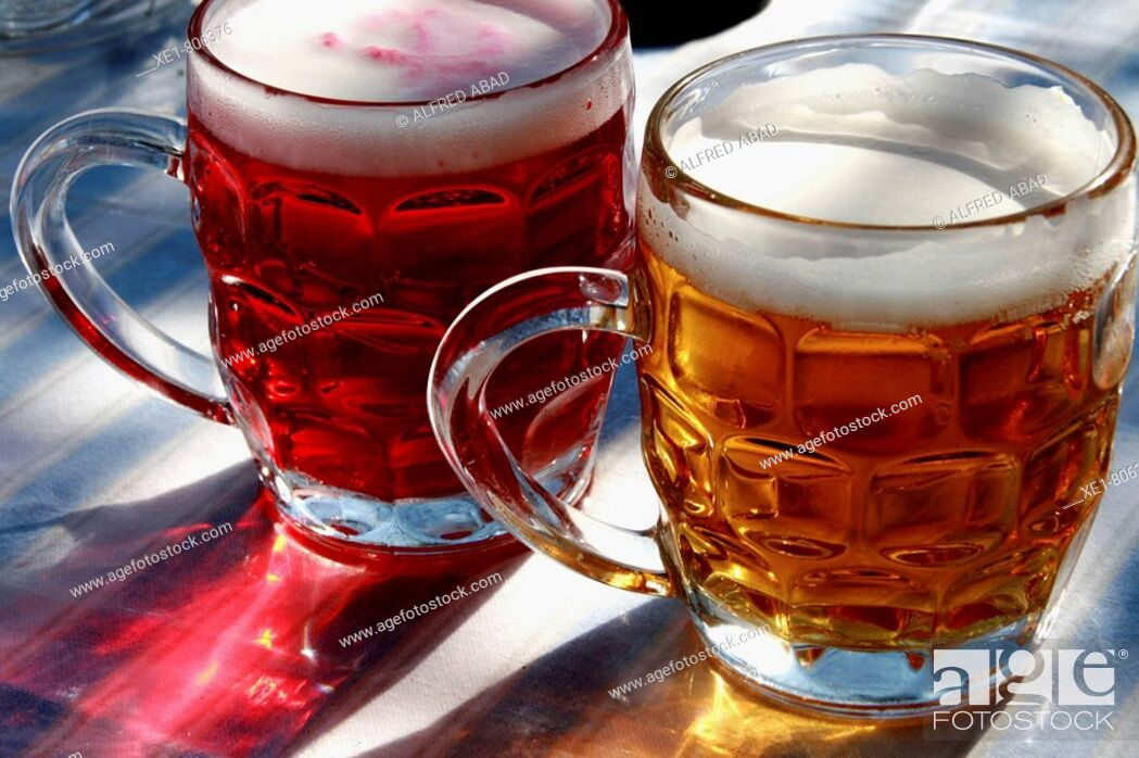 Stock Photo: Beer and redcurrant beer in dimpled glass jugs.