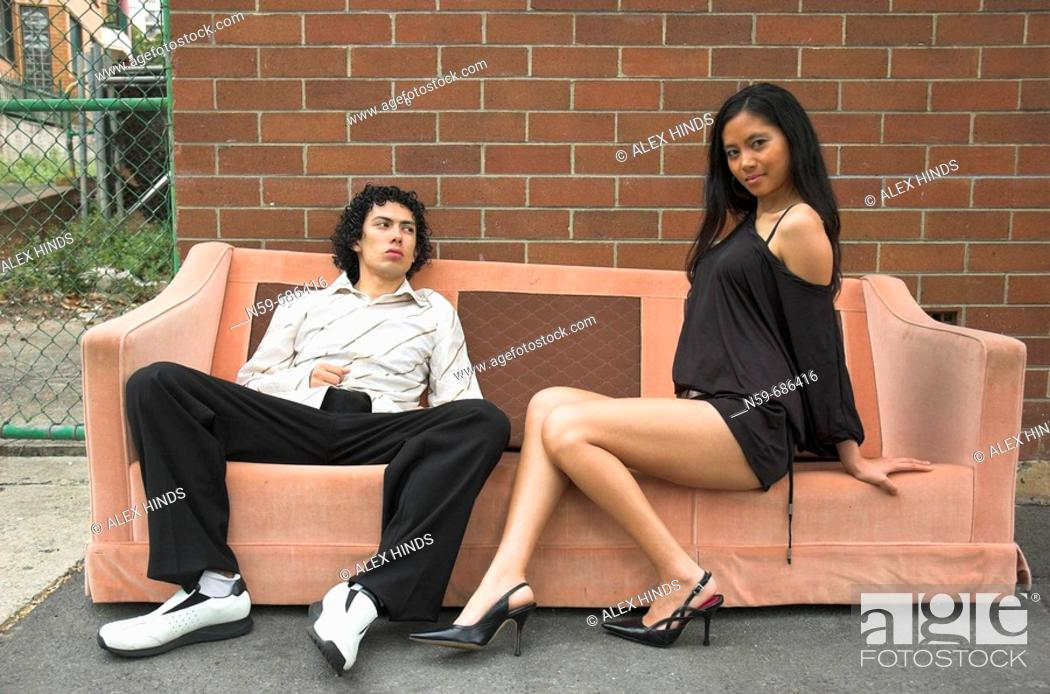 Stock Photo: Two young party people pose on an old sofa in the street.