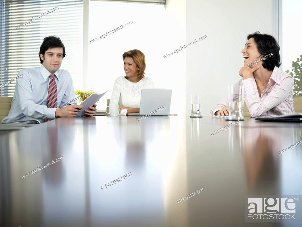 Stock Photo: Three businesspeople having meeting in conference room low angle view.