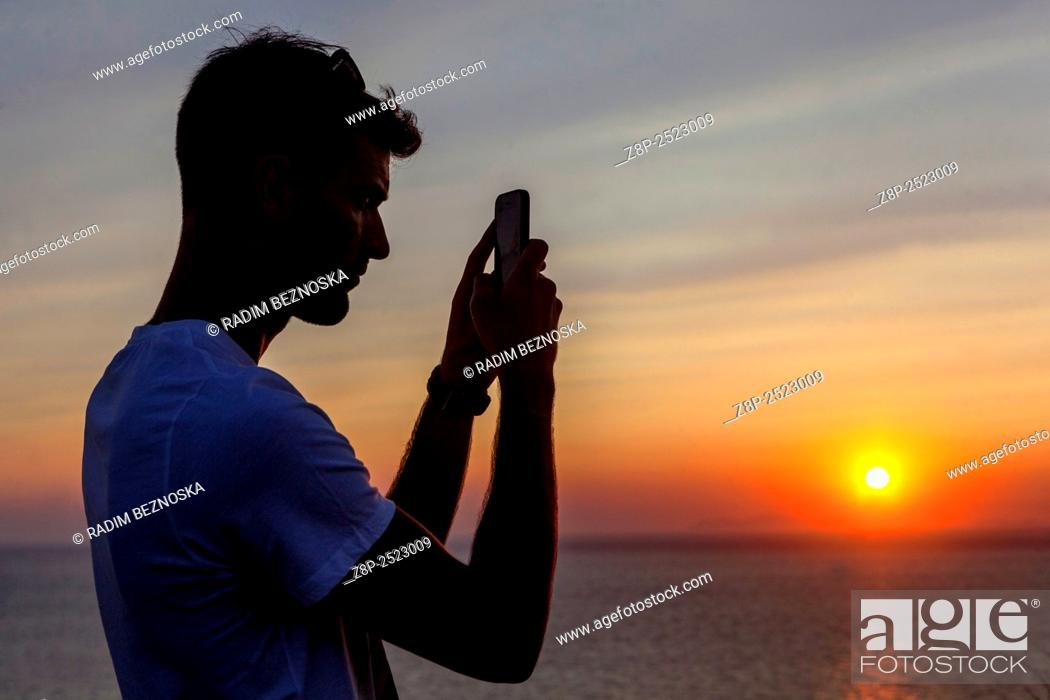 Imagen: A young man filming sunset on his cellphone, Oia, Santorini, Greece.