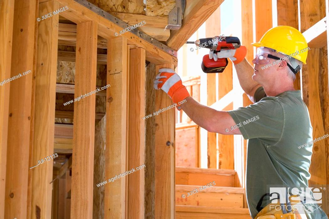 Stock Photo: Builder in hardhat drilling, side view.