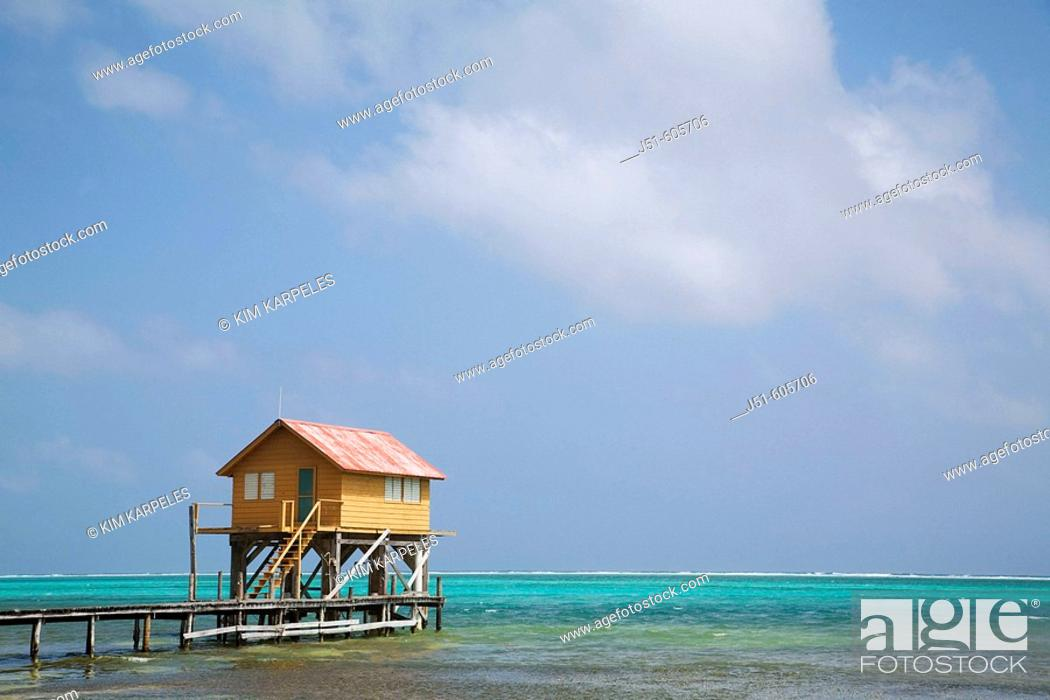 Stock Photo: BELIZE San Pedro on Ambergris Caye   Colorful wooden building on stilts, end of dock, Caribbean waters.