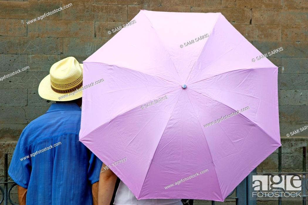 Stock Photo: Tourist looking at a wall while sheltering under an umbrella, Temple of Heaven, Beijing, China.