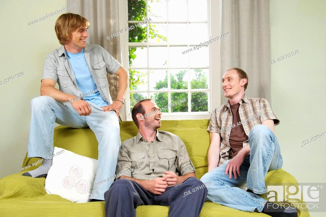Stock Photo: Three young men lounging on couch.