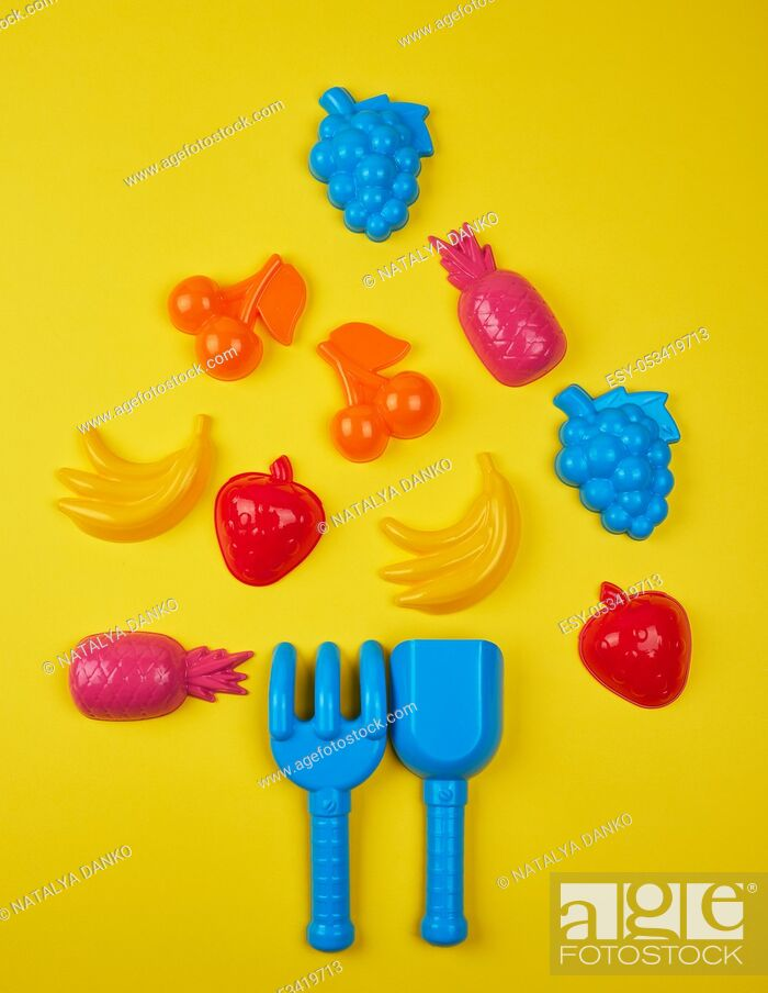 Stock Photo: children's plastic multi-colored toys laid out in the form of a Christmas tree, festive backdrop.