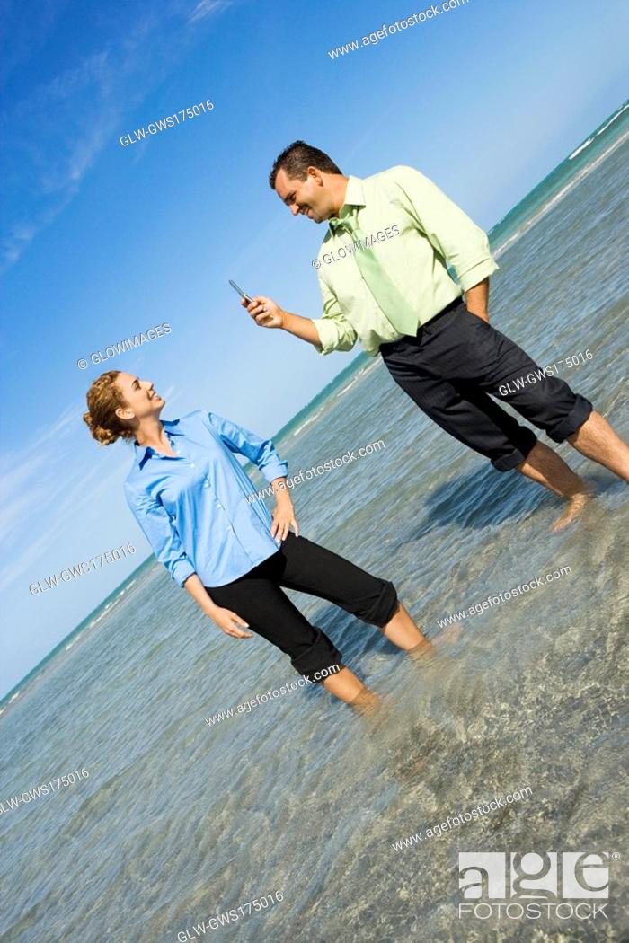Stock Photo: Mid adult man taking a photograph of a mid adult woman on the beach.