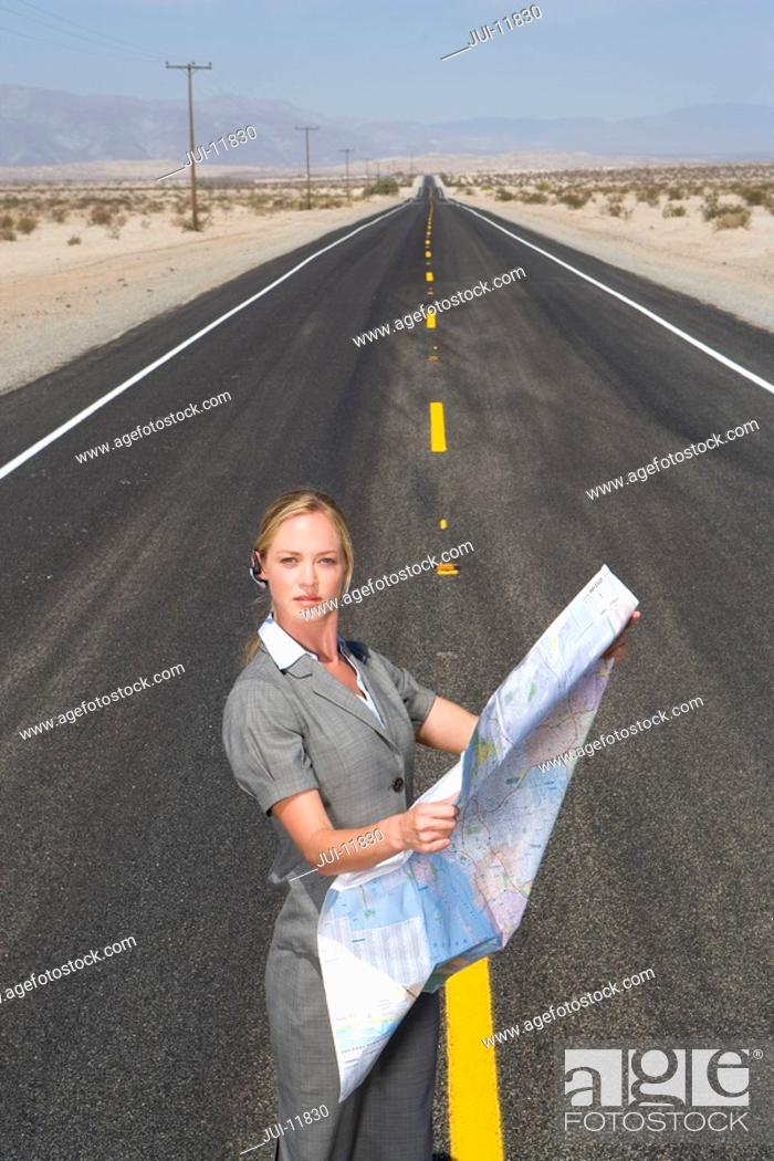 Stock Photo: Businesswoman in middle of open road in desert with road map, portrait, elevated view.