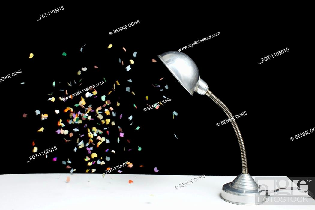 Stock Photo: Confetti floating next to a table lamp.