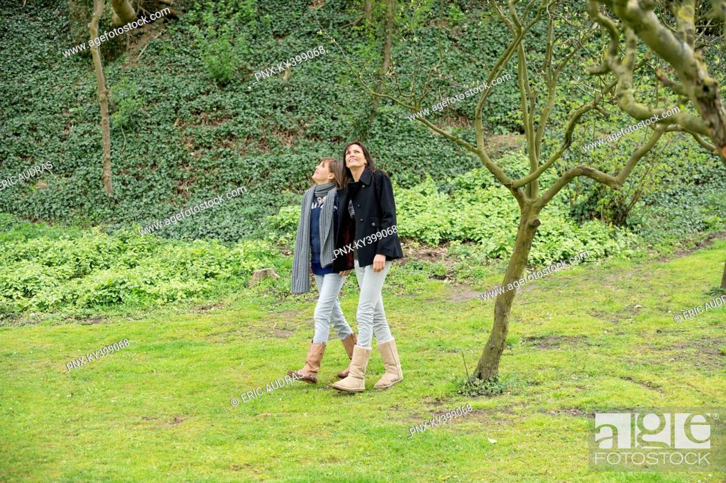 Stock Photo: Woman with her daughter walking in an orchard.