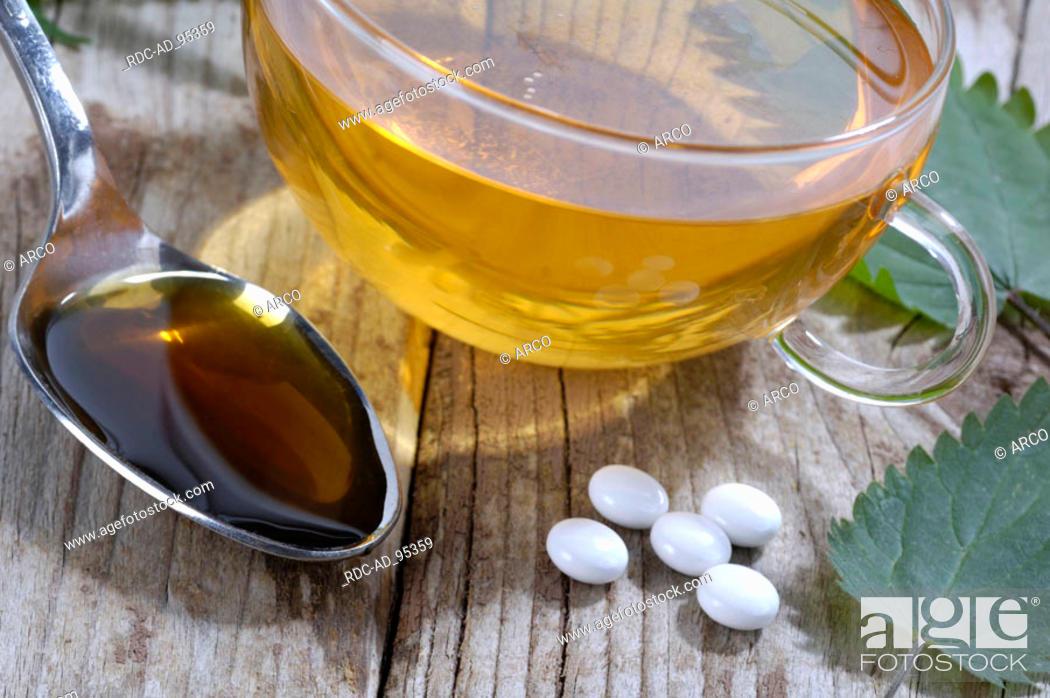 Photo de stock: Cup of tea Nettle juice and Nettle pills Urtica dioica.