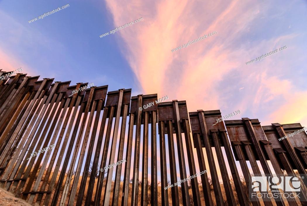 Stock Photo: Sunset at United States border fence, US/Mexico border, east of Nogales, Arizona, USA.
