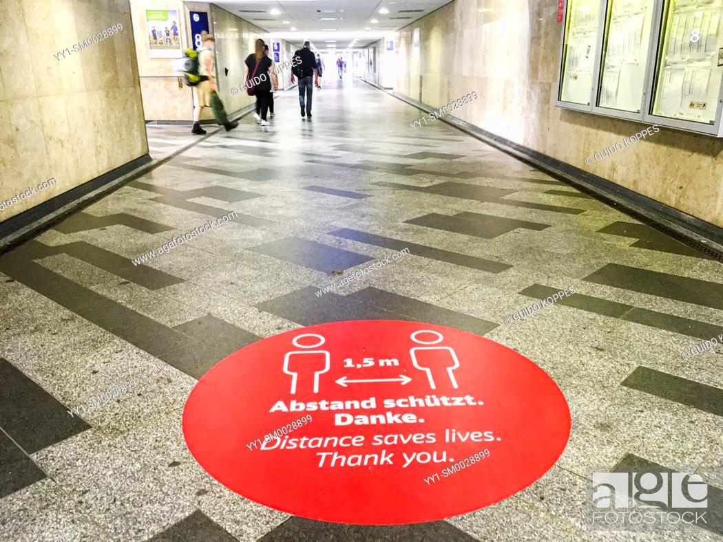 """Stock Photo: Berlin, Germany. A: """"""""Bitte Abstand Halten"""""""", or: """"""""Keep Your Distance"""""""" sing on the ground of an Ostbahnhof Station."""