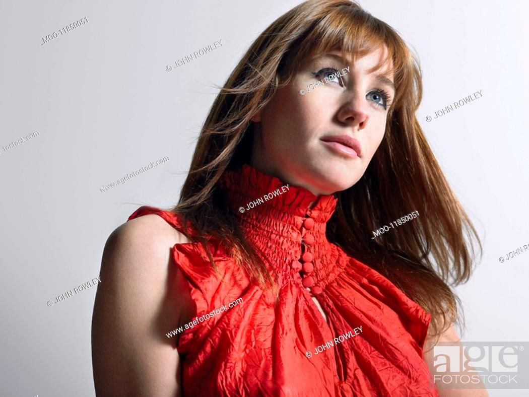 Stock Photo: Woman in red top in studio head and shoulders.