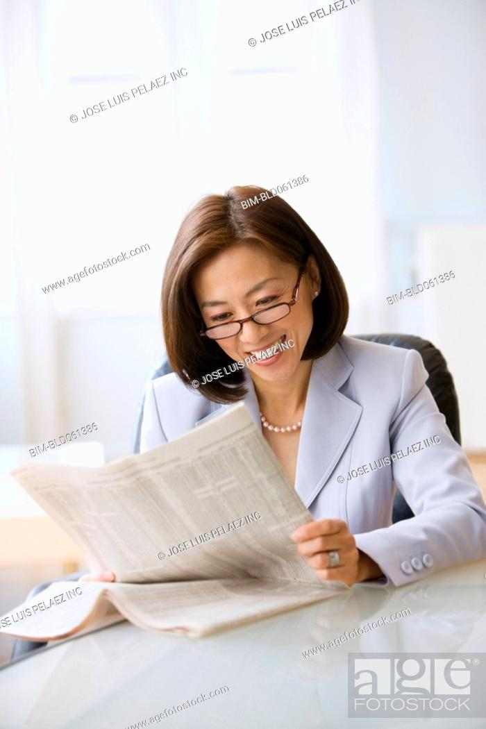 Stock Photo: Asian businesswoman reading newspaper.