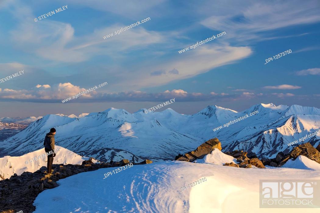 Photo de stock: Hiker on a ridge in the Alaska Range on an early summer evening; Alaska, United States of America.
