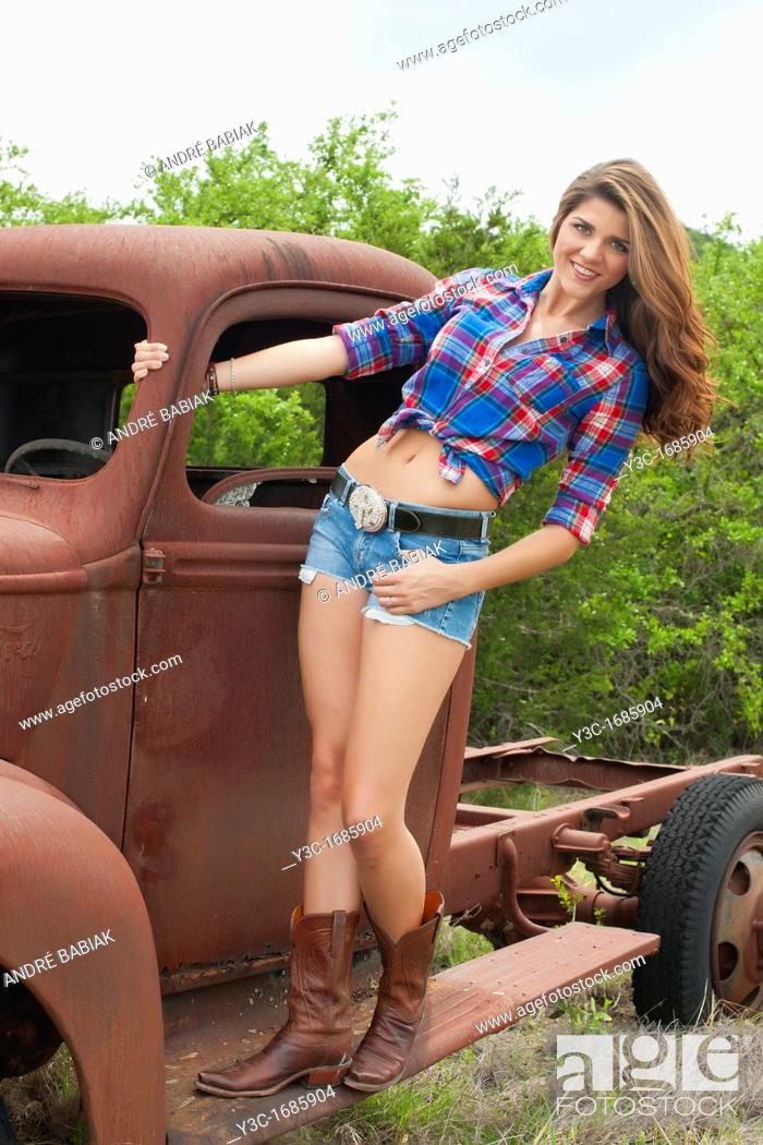 Stock Photo: American country girl posing on old rusty farm truck.