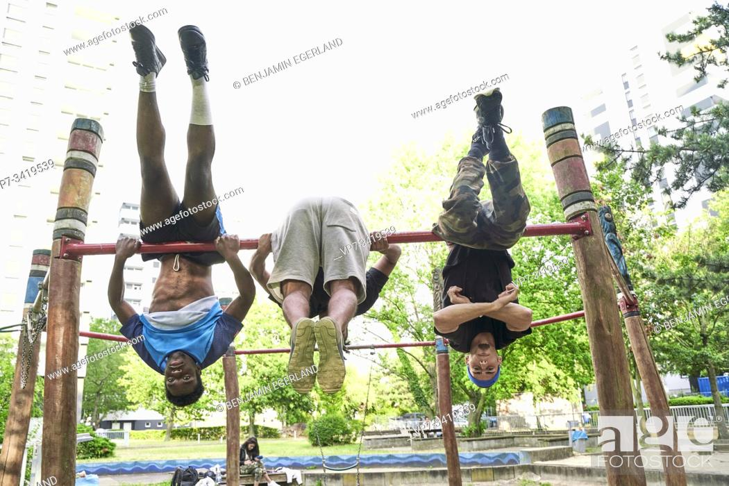 Stock Photo: Young men doing acrobatics in park. Frankfurt am Main, Germany.