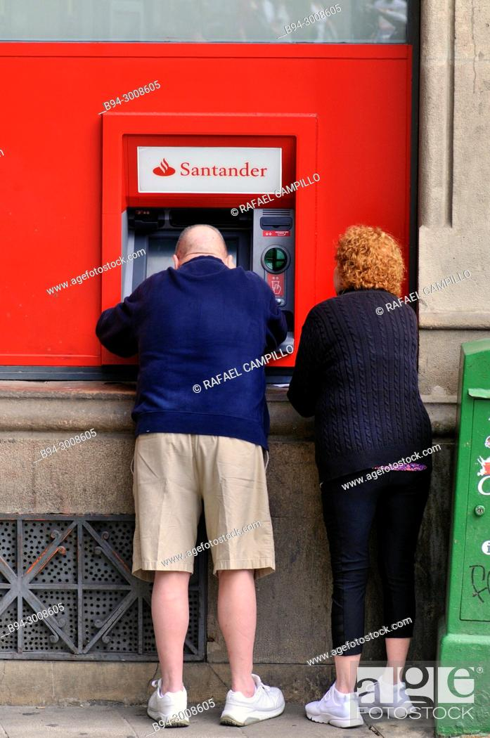 Stock Photo: Couple in a ATM. Barcelona, Catalonia, Spain.