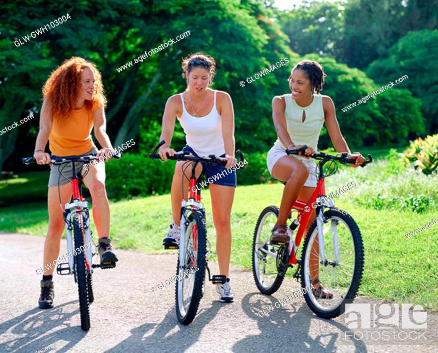 Stock Photo: Three young women cycling, Bermuda.
