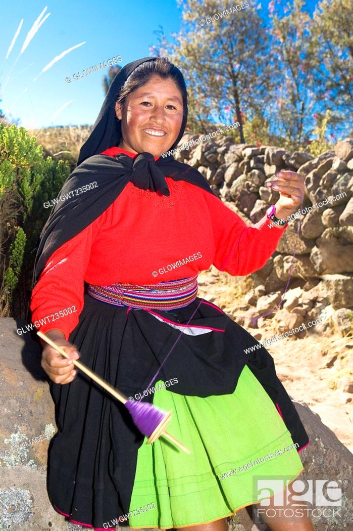 Stock Photo: Portrait of a young woman spinning a reel of thread, Taquile Island, Lake Titicaca, Puno, Peru.