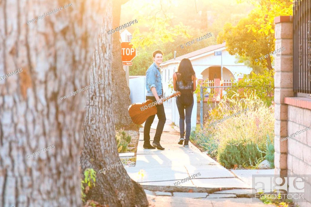 Imagen: Young couple walking outdoors, young man holding guitar.