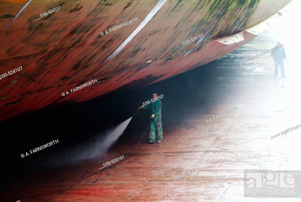 Stock Photo: Pressure washing the hull of a tanker in dry dock. Antwerp. Belgium.