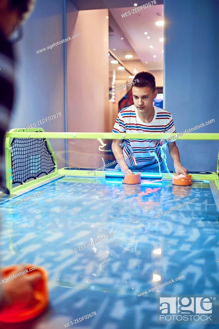 Stock Photo: Teenage boy playing air hockey in an amusement arcade.