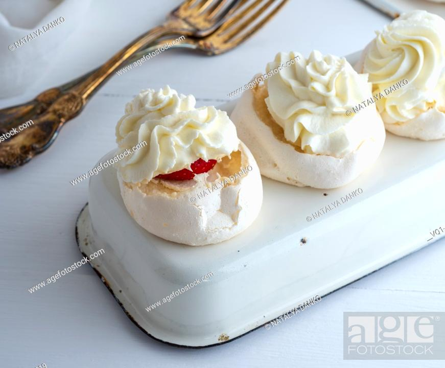 Imagen: baked meringue with cream and fresh strawberries on an iron tray, close up.