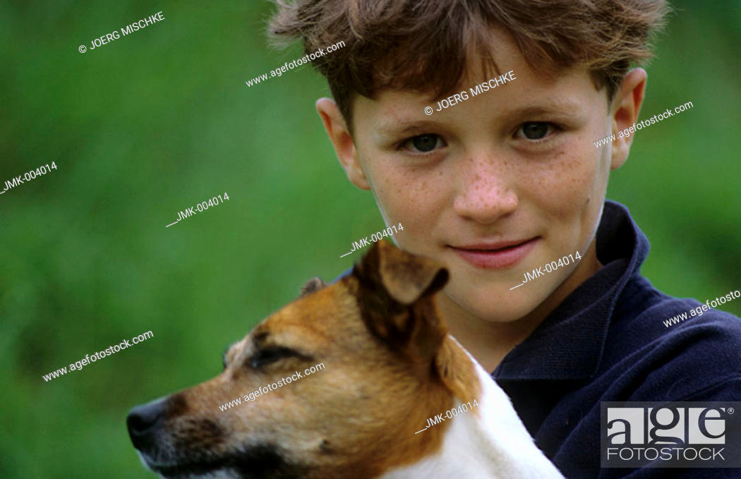 Stock Photo: A boy, 5-10 years old, and a dog outside.