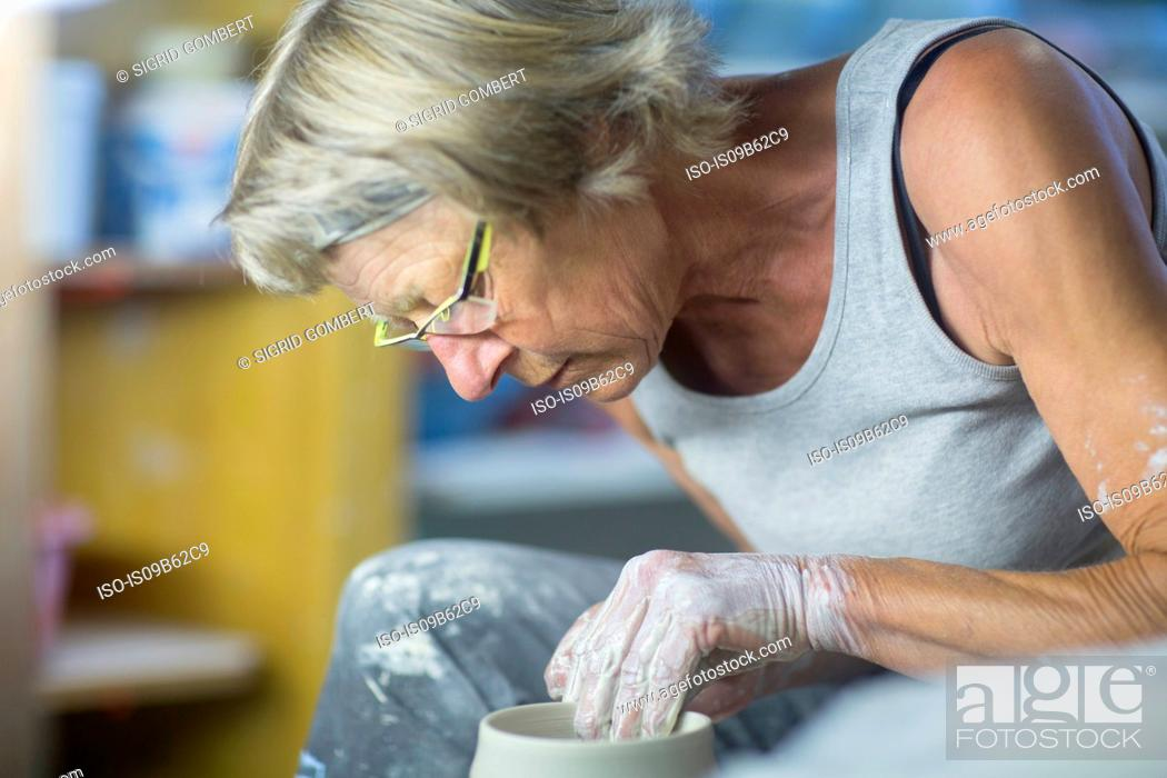 Photo de stock: Senior woman in pottery workshop, at potters wheel, making bowl, close-up.