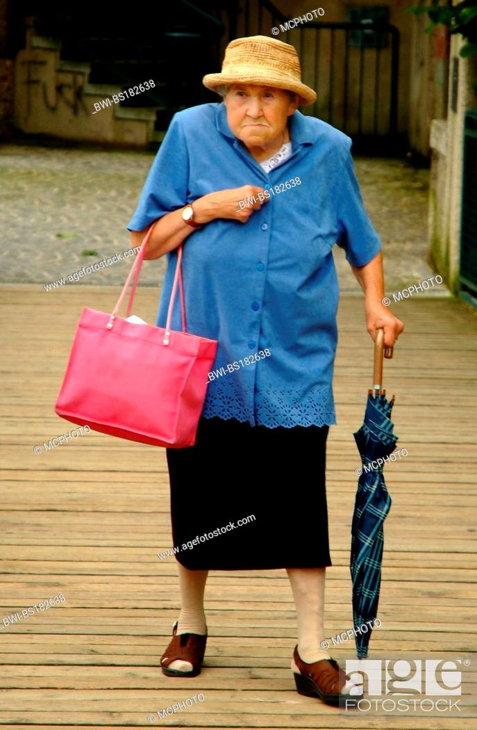 Stock Photo Grim Old Lady With An Umbrella And Bag