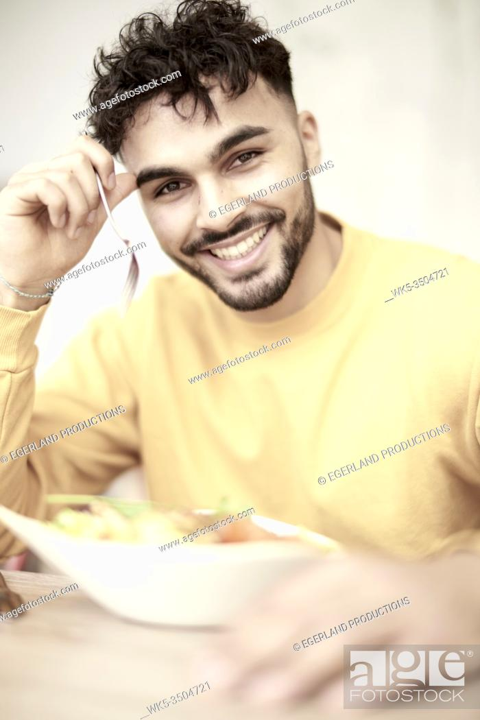 Stock Photo: Young man sitting at table in restaurant, eating salad.