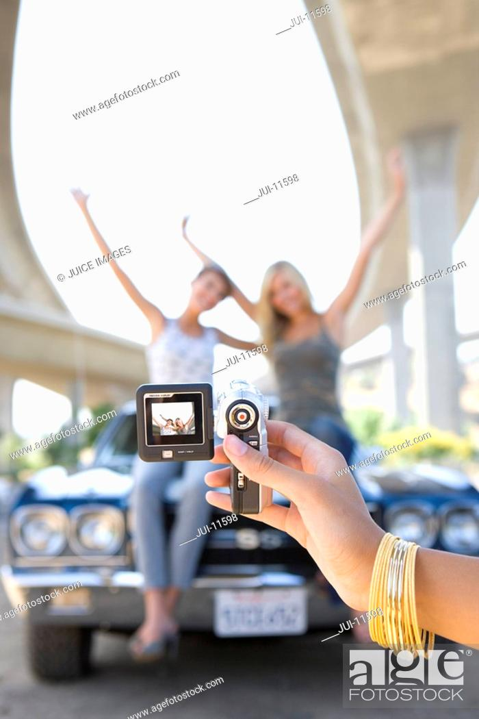 Stock Photo: Young woman taking photograph of friends on bonnet of car beneath overpass, close-up of hand.