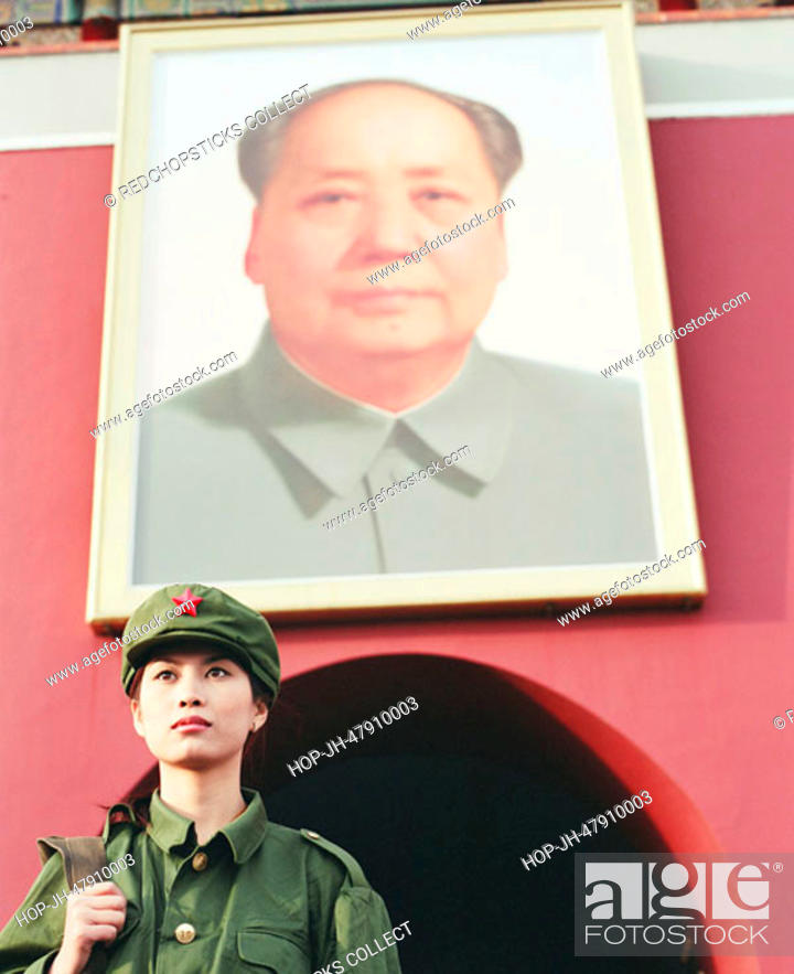Stock Photo: Low angle view of a young woman in army uniform standing in front of a palace, Forbidden Palace, Beijing, China.