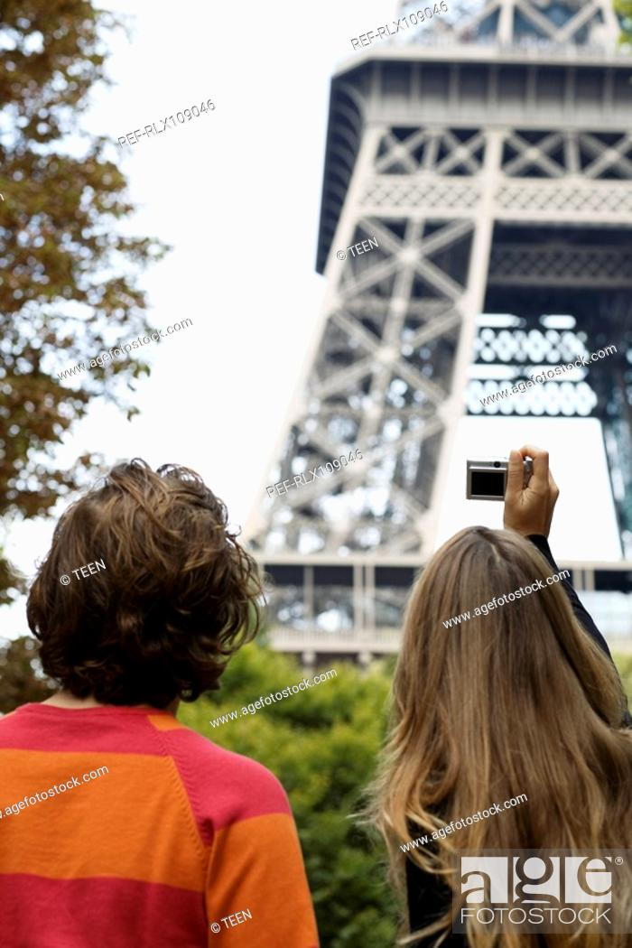 Stock Photo: Rear view of young couple taking picture of Eiffel tower, Paris, France.