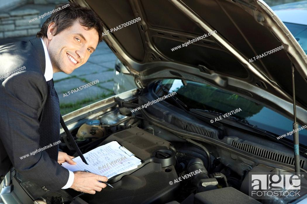 Stock Photo: Inspecting car engine.