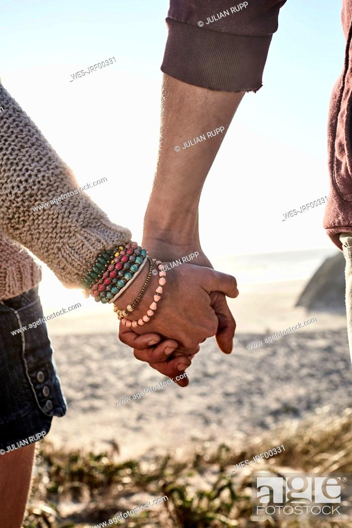 Stock Photo: Portugal, Algarve, close-up of couple holding hands at sunset on the beach.