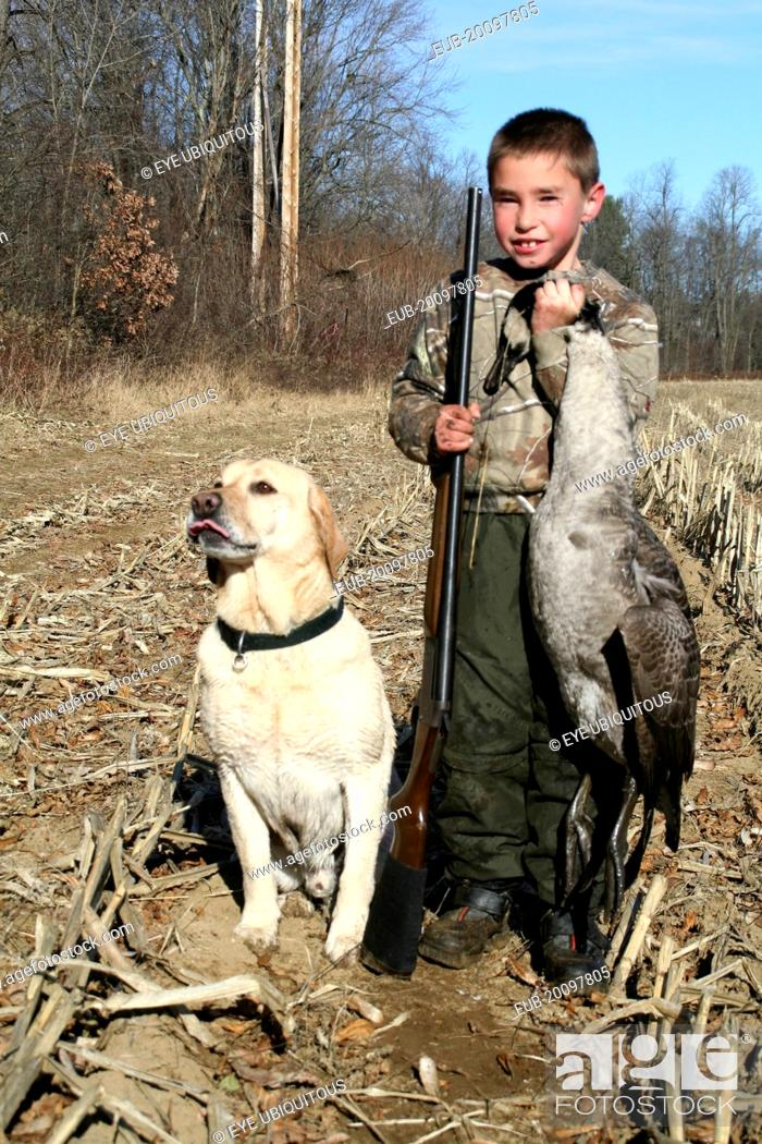 bf1757257 Stock Photo - Tyler Stone 8 year old boy Cooper yellow labrador retreiver  pet dog goose hunting boys first goose.