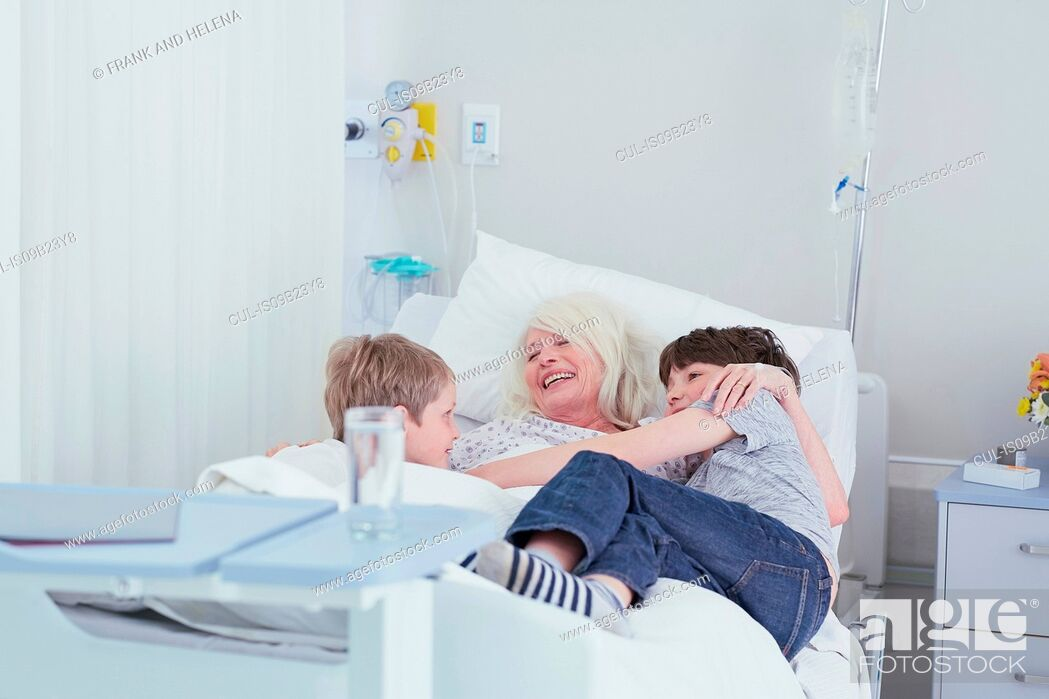 Stock Photo: Senior female patient cuddling grandsons on hospital bed.