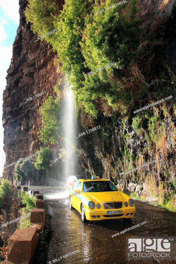 Stock Photo: Taxi driving through waterfall at the old coastal road, also called the car washing street, Madeira, Portugal, Europe.
