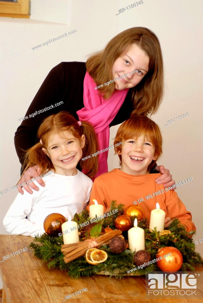 Stock Photo: Young woman with children is lighting candles on an advent wreath.