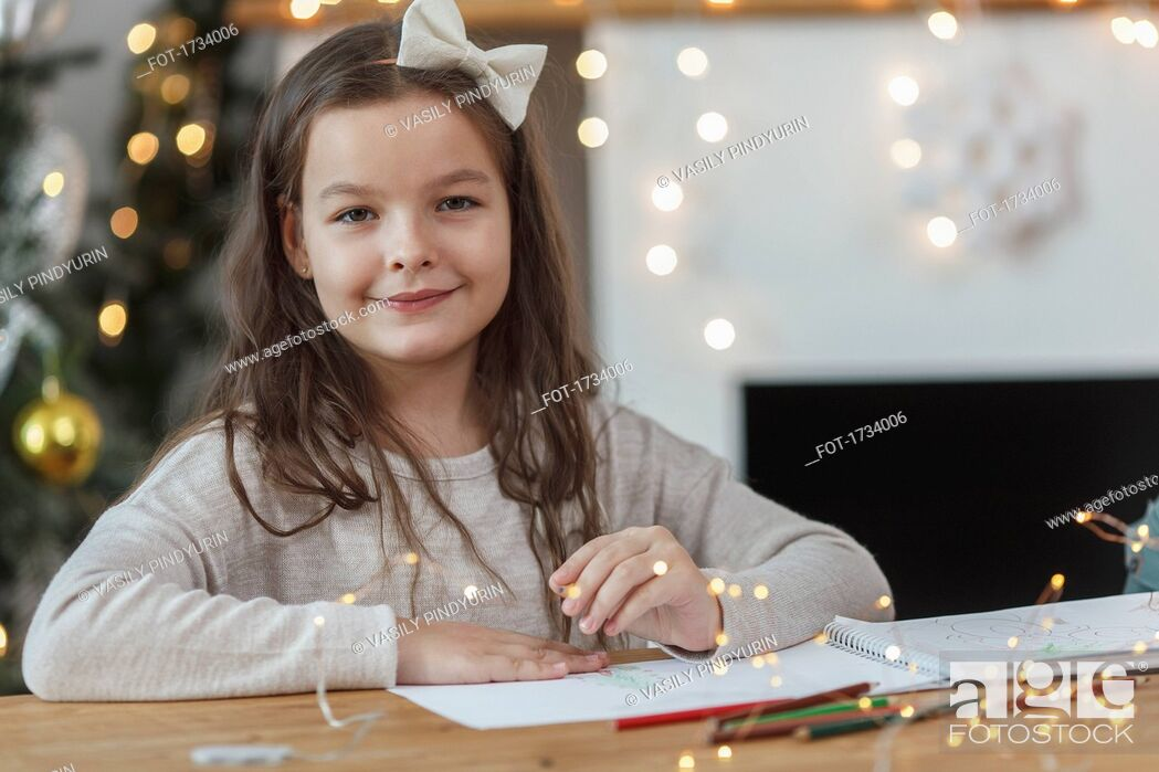 Stock Photo: Portrait of smiling girl sitting at table with illuminated string lights.