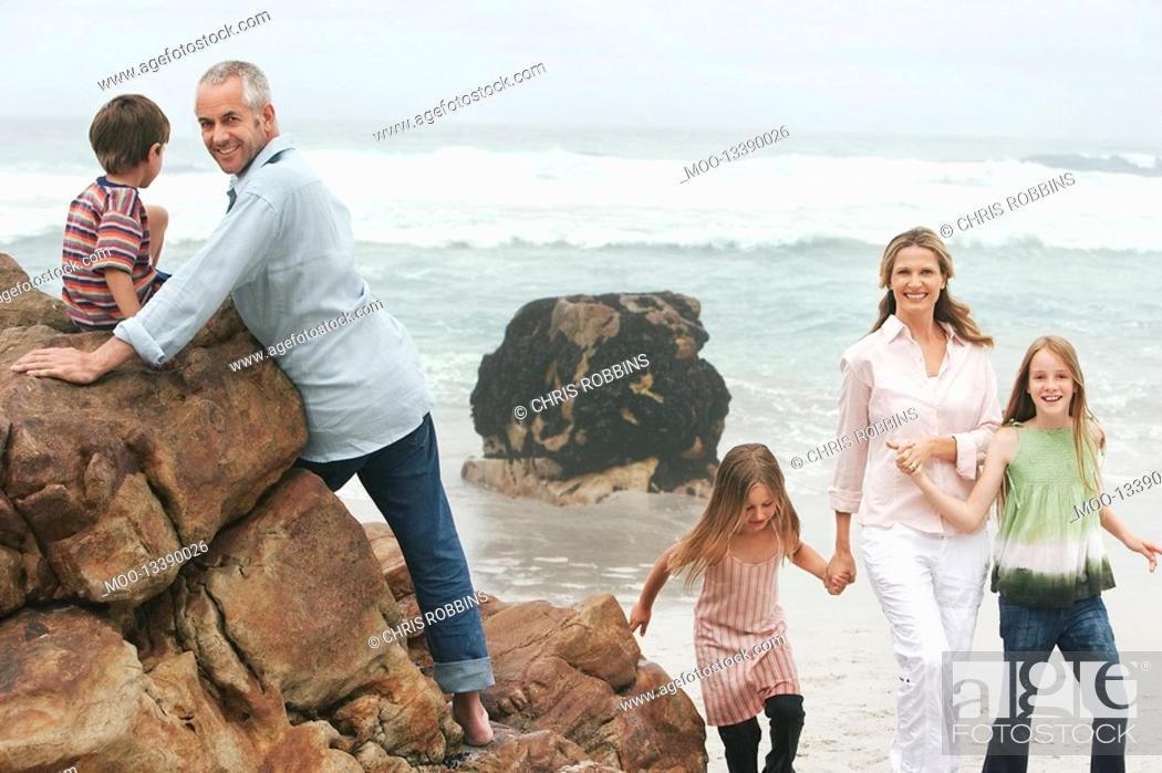 Stock Photo: Family with three children 5-6 7-9 10-12 on beach.