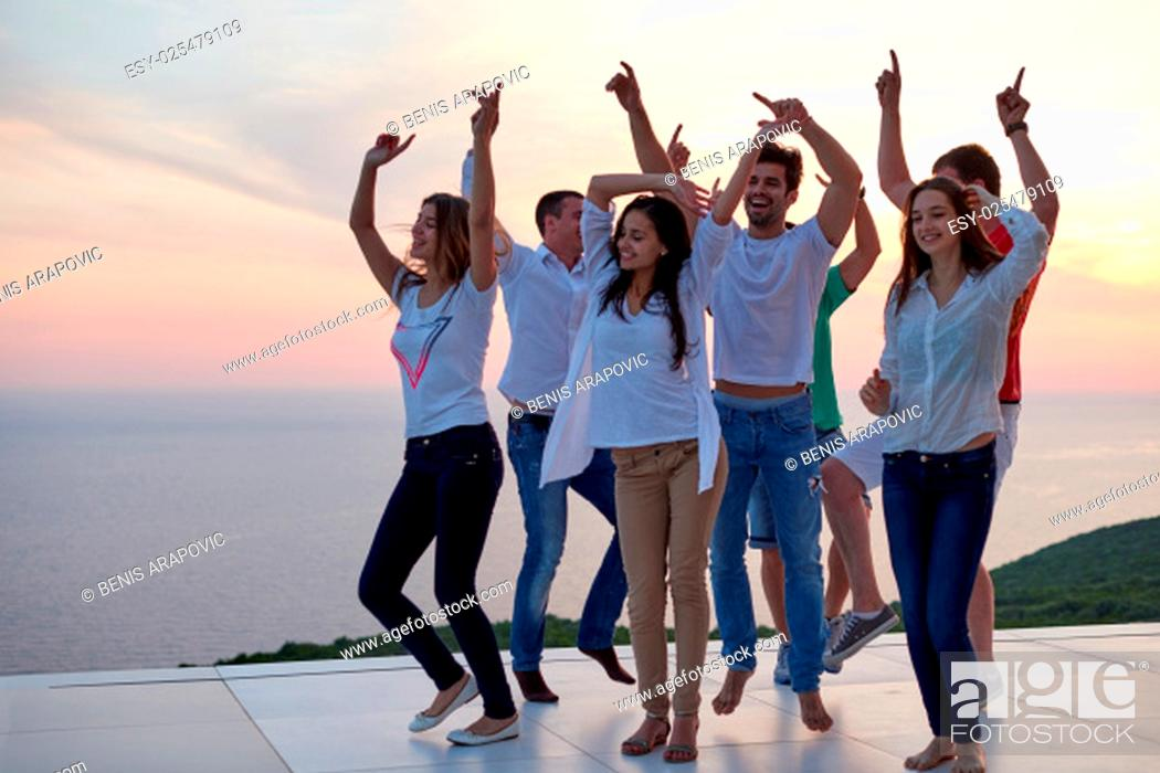 Stock Photo: group of happy young people dancing and have fun on party in modern home bacony with sunset and ocean in background.